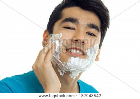 Portrait of a handsome young guy who smiles at the camera and hand shaving foam on your face isolated on white background