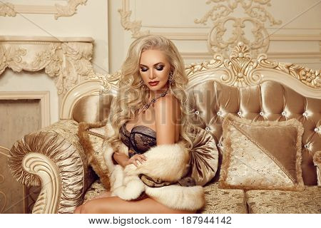 Beautiful Alluring Blond Woman In Fur Coat Sitting On Royal Sofa In Luxury Modern Interior. Beauty G