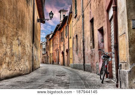 Imola, Bologna, Italy: narrow street at sunset in the old town with bicycle, street lamp, colored houses and bell tower