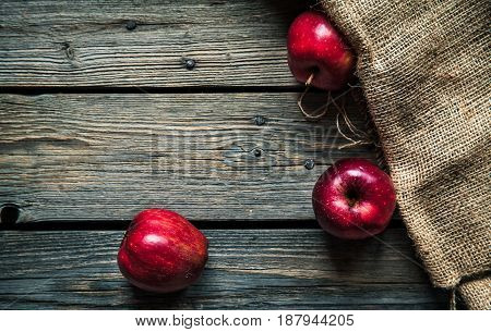 Red apples on a wooden background with sacking. fruit, natural food