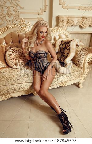 High Heel Shoes. Beautiful Alluring Blond Woman In Sexy Lingerie With Long Legs On Royal Sofa In Lux