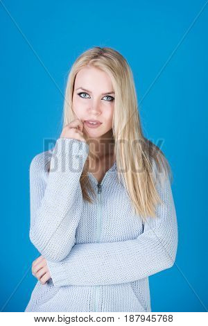 woman or cute girl with long blond soft dry dye hair and adorable face stylish makeup posing in fashionable sweater on blue background. Fashion and beauty
