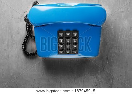 landline blue phone on a gray wall background