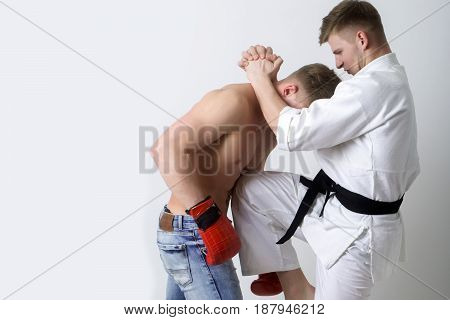 Karate Athlete In Kimono Kicking Knee At Boxer