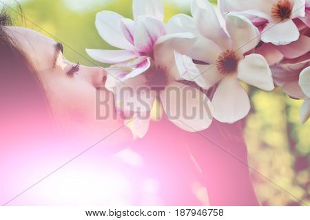 girl or cute woman with long brunette hair smelling pink blossoming magnolia flowers from tree in spring park on sunny day on blurred floral environment. Springtime. Youth. Beauty