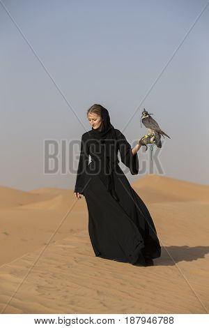 woman in abaya with a peregrine falcon