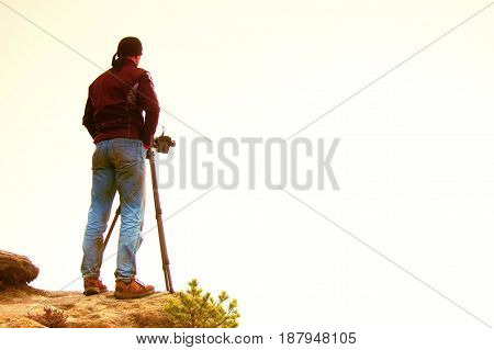 Silhouette Of A Landscape Photographer On The Rocky Peak Above Misty Valley