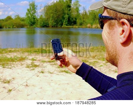 Man Is Sitting On The Beach At Lake And Writing A Sms On His Smart Phone