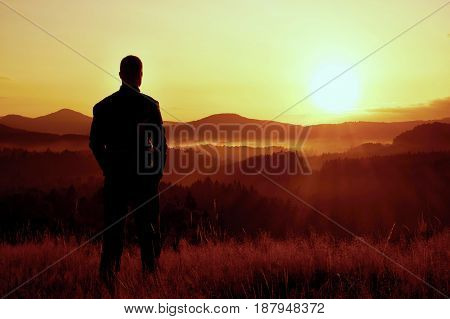 Tall Hiker Stand On Meadow With Golden Stalks Of Grass And Watch Over Valley To Sunrise