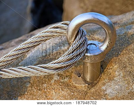 Detail Of Steel Bolt Anchor Eye In Rock. The End Knot  Of Steel Rope. Climbers Path In Rocks Via Fer