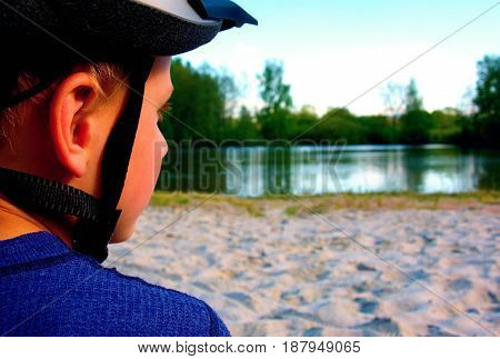 Small Boy With A Bicycle Helmet Head, Dressed In Sportswear On Beach