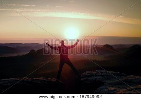 Jumping Hiker In Black Celebrate Triumph Between Two Rocky Peaks. Wonderful Daybreak With Sun Above