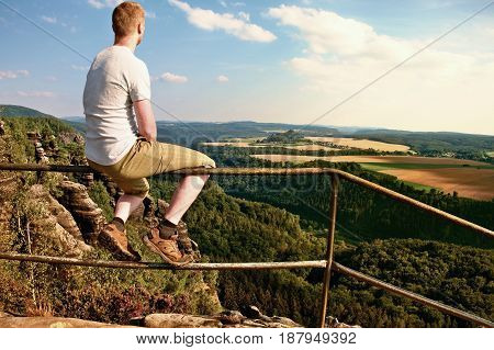 Ginger Man Sit On Handrail At Peak Of Rock And Watch To Landscape.  Sunny Day In Rocky Mountains. Hi