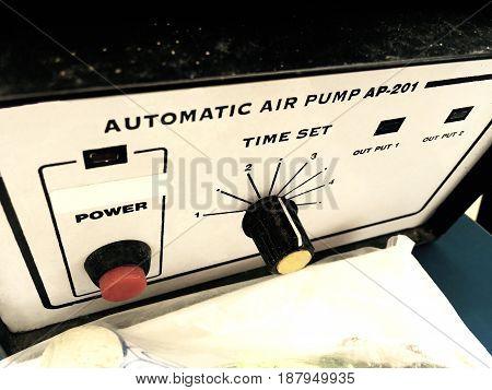 Close Up of Automatic Air Compressor Pressure Pump Tool for Auto Repair Shop.