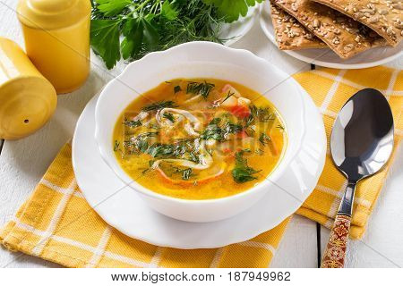 Homemade surimi soup with potatoes carrots onions and herbs. On wooden table served soup in white bowl dill and parsley cracker with pumpkin and sunflower seeds yellow pepper and salt containers