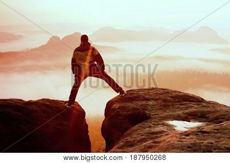 Hiker In Black Is Jumping Between The Rocky Peaks. Wonderful Daybreak In Rocky Mountains, Heavy Oran
