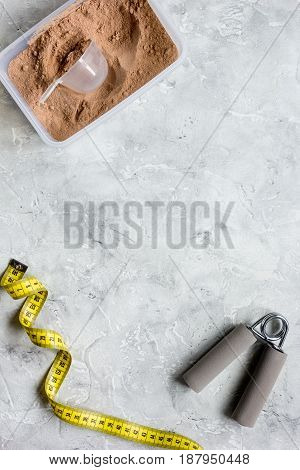 sport diet nutrition and fitness equipment , bars and measure tape on stone background top view mock up
