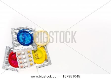 condoms and pills for male contraception and birth control on white background top view mockup