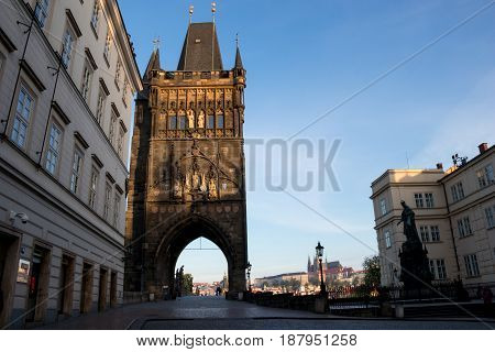 PRAGUE CZECH REPUBLIC - MAY 10 2017: The Old Town Bridge Tower leading to the Charles Bridge with Prague Castle in the background and the statue of King Charles IV in the foreground