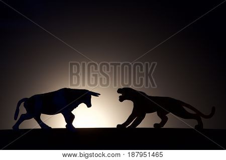 concept conflict.Bull versus tiger silhouette on a dark background