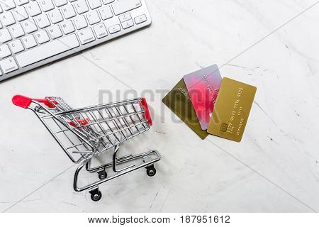 online purchasing with mini trolley and credit cards on light office desk background top view