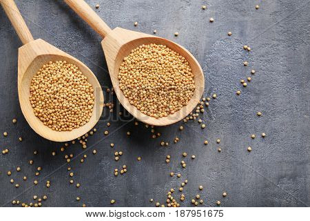 Mustard seeds in wooden spoon on grey table