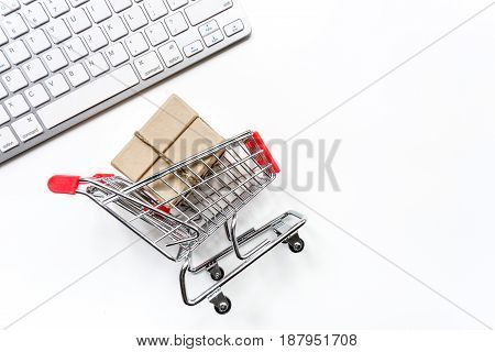 online purchasing with mini trolley on white office desk background top view mock up