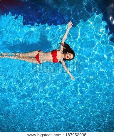 Top View Of Fashion Sexy Bikini Tanned Model In Blue Water Swimming Pool On Luxury Resort. Beautiful