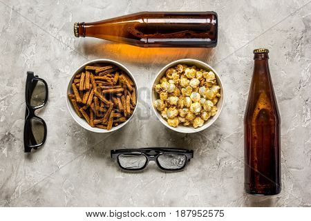 home party with TV watching, snacks, pop corn, chips and bread crumbs and beer on stone background top view