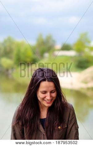 Young beautiful woman without make-up with dark long hair smiling near the lake.