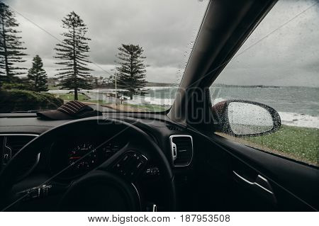 Inside car cockpit view with the coastline in the background.