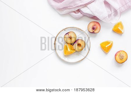 woman summer breackfast with orange and peach fruits and pink fabric on white desk background flat lay mockup