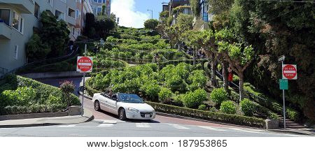 San Francisco, California - April 13, 2017. A car is coming down famous Lombard street.