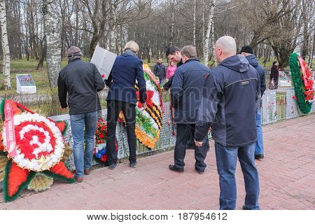Kirishi, Russia - 9 May, A group of people attaching a wreath, 9 May, 2017. Laying wreaths and flowers in memory of the fallen at the Eternal Flame.