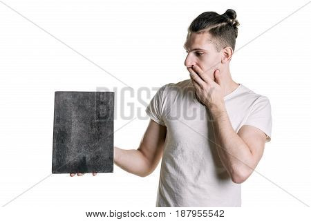 A Young Handsome Guy With An Empty Gray Plaque, Looking At The Plate With Astonishment. Place For Si