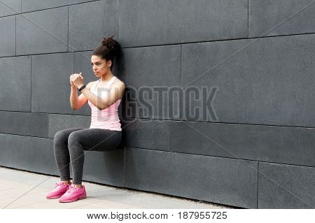 Athlete doing wall squat on city street