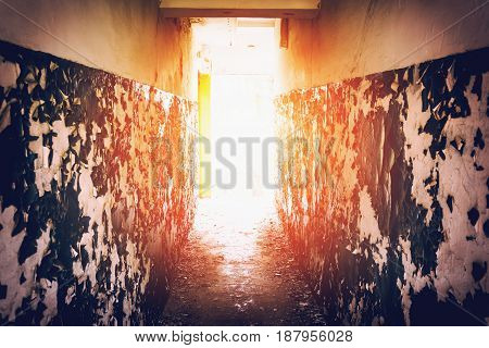 Corridor with peeling walls, light at the end of the tunnel concept