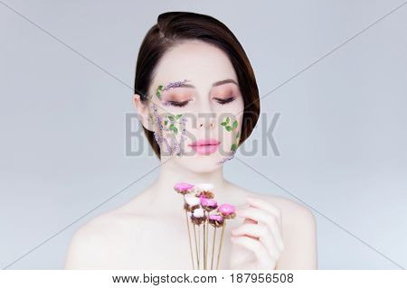 portrait of beautiful young woman with flowers on her face holding dried flowers on the wonderful grey studio background
