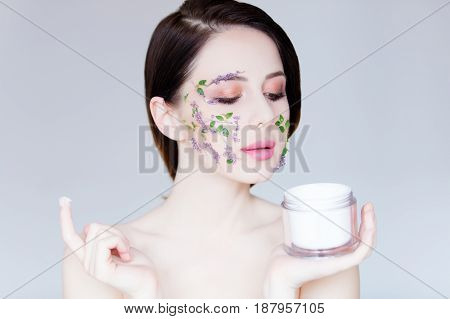 portrait of beautiful young woman with flowers on her face holding cream on the wonderful grey studio background