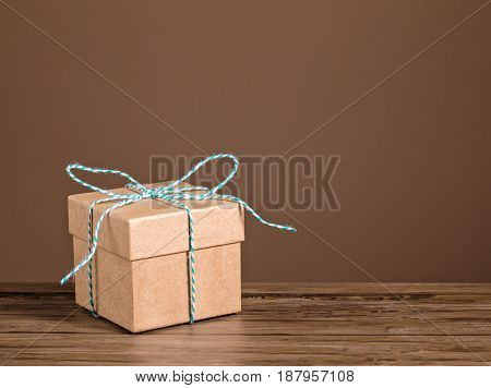 Brown gift box with blue string tied in a bow on a wooden table.