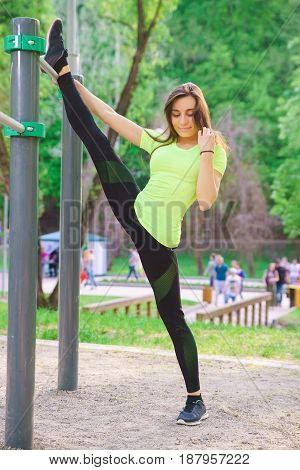 Sports girl brunette in the park is engaged in fitness, warm-up