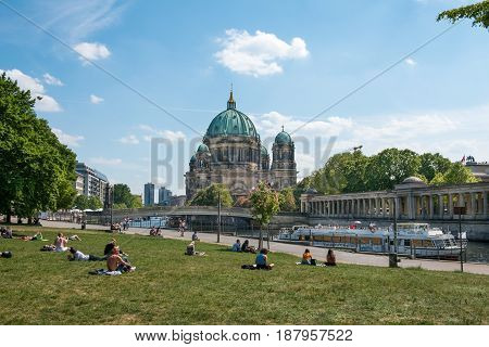 People Relaxing On Meadow In Park  In Berlin With The Berlin Cathedral In Background