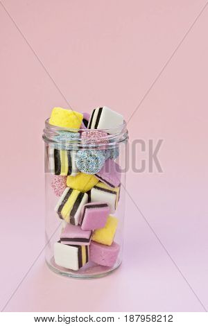 Small glass jar with colored chewing sweets on the pink background, minimalism concept