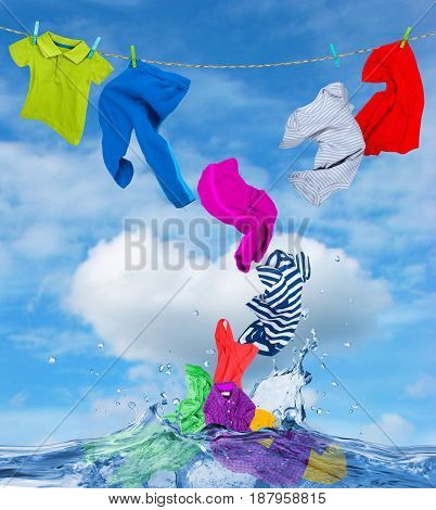 Colorful clothes fly out of the water against the background of a cloudy sky