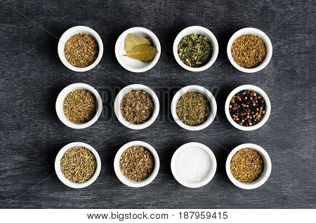 Overhead shot of rows of dried herbs salt and peppercorns in small bowls on a dusty textured chalkboard surface.