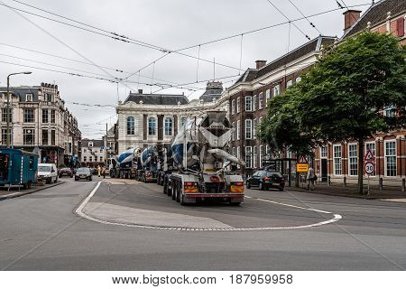 The Hague The Netherlands - August 7 2016: Street view in the Hague with convrete trucks near a construction site a cloudy day of summer.