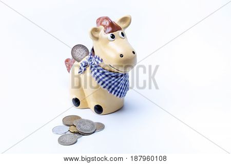 Brown Country Horse Piggy Saving Bank Moneybox With Coins In The Front Of It Isolated On White Backg