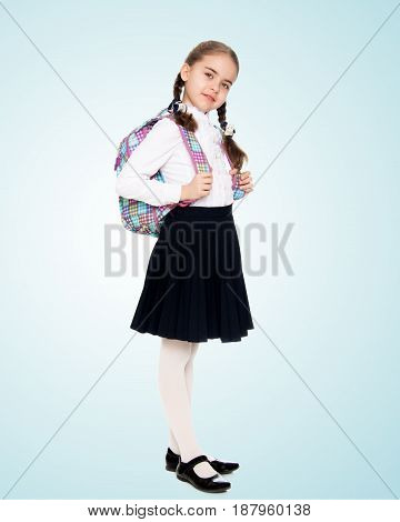 Beautiful little blond schoolgirl, with long neatly braided pigtails. In a white blouse and a long dark skirt.She wears a school satchel.On the pale blue background.