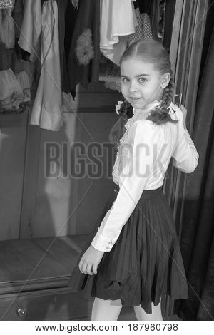 Beautiful little schoolgirl girl with braided braids on her head, in a white blouse and black skirt. She opens the wardrobe door with her hand. The girl picks up her clothes.Black-and-white photo. Retro style.
