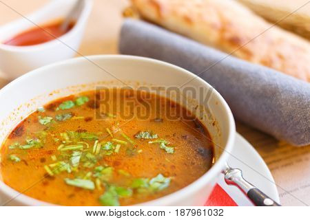 Soup kharcho sprinkled with fresh herbs. Traditional Georgian soup Kharcho with meat and rice on old wooden background. Selective focus.